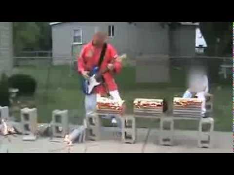 何してはるんですか? ギターを弾きながら燃える瓦を割る男性